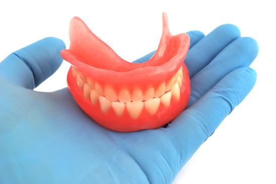 dentures in hand